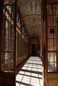 einer der Gänge des Gebäudes, verglaste Holztüren, große Fenster und bemalte Decken