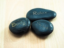 drei schwarze Steine mit der Aufschrift Body Relax und Soul auf Holztisch