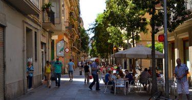 Fussgängerzone in Poble Sec , Terrasse eines Cafés mit weisen Sonnenschirm