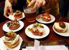 Tisch mit sechs verschiedenen Tapas und zwei Hände der Kellnerin die gerade eine Casa dazu serviert