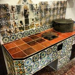 Teil einer Küche mit einem grossen alten Topf, alle Oberflächen sind gefliest und an der Wand in der Mitte ist die Königin dargestellt