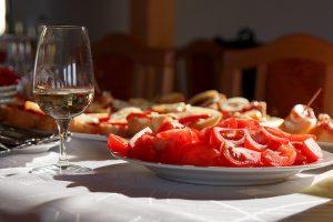Tisch mit weisser Tischdecke, ein Weinglas mit Weisswein und ein weisser runder Teller voll mit geschnittener Tomaten
