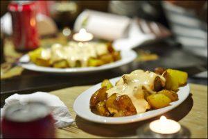 Nahaufnahme eines Tisches in einer Tapasbar mit einem ovalen weissen Teller mit Patatas Braves und einem angezündetem Teelicht