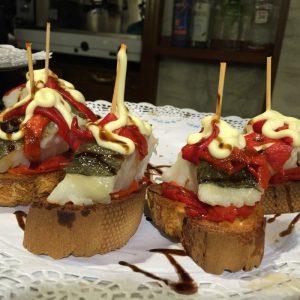 Teller mit fünf Pintxos aus Baguette, Kabeljau und gebratene Paprika