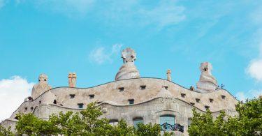Aussicht von unten nach oben auf das Casa Mila mit grünen Bäumen davor und blauem Himmel darüber