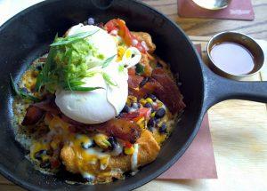 eine mittelgroße Gußpfanne mit Gemüseeintopg und ein pochiertes Ei oben drauf