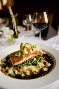 ein großer Tisch mit weisser Tischdecke, einer Rotweinflasche und mehreren Weingläsern, aber fokussiert ist ein tiefer Teller mit einer dunklen Sauce, Gemüse und einem Lachsfilet oben drauf