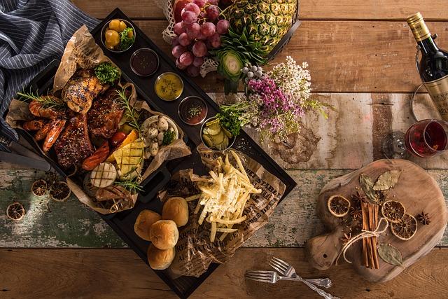 ein Holztisch auf dem ein Tablett mit Brot, Pommes, verschiedenen Sossen, Fleisch und Gemüse seht, recht oben ein Korb mit Obst und rechts unten zwei aufeinanderliegende Gabeln und ein kleines Holzbrett mit Zimtstangen und Orangenscheiben