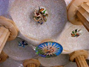 Gewölbte Decke von innen gesehen des Gebäudes im Gaudi Park, aus weissen Mosaiken mit bunten Verzierungen