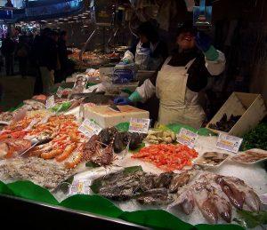 Verkäuferin an ihrem Fischstand mit Muscheln, Garnelen, Tintenfisch, Langusten, Hummer und vieles mehr