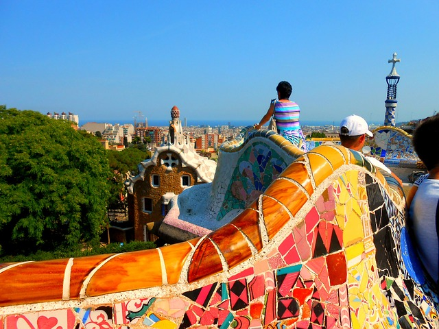 Leute auf den bunten Bänken die die Aussicht auf Barcelona geniessen