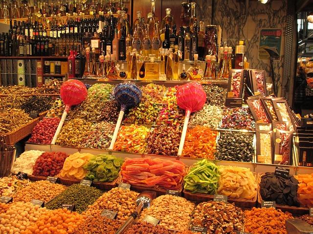 Ein Verkaufsstand mit getrockneten Früchten und drei Riesen Lutscher aufgereiht auf der Ware