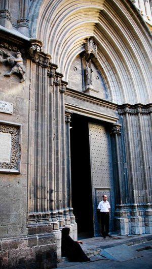 der imponente Eingang der Kathedrale Barcelonas, nur ein Türflügel ist geöffnet und vor dem Geschlossenen steht ein Mann mit schwarzer Hose und weissem Hemd