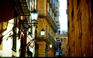 Einsicht in eine enge Gasse des gotischen Viertels, die Gebäude haben mehrere Stockwerke, große Fenster und kleine Balkons, das Sonnenlicht erweckt den Eindruck, dass die Laternen an sind
