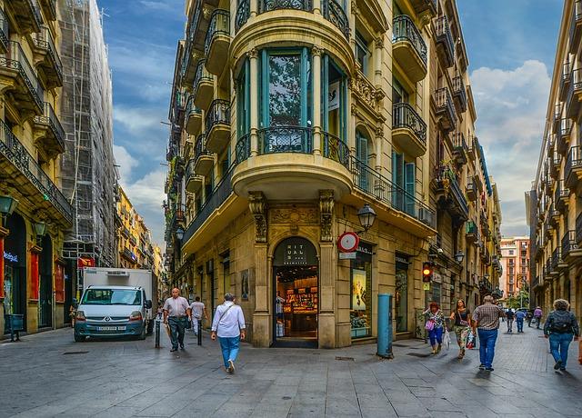 eine Kreuzung and der zwischen zwei Strassen ein grosses gomd-türquis farbiges Gebäude steht, links fährt ein weises Auto und über die Kreuzung laufen vereinzelte Fussgänger