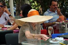 Ältere Dame mit einer riesen Pamela mit orangenem Tuch die ein Glas Sekt auf der Terrasse eines Restaurants trinkt
