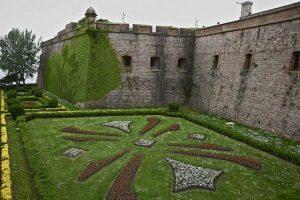 Teil der Mauern des Schlosses mit einem Vorgarten auf dem ein abstraktes Symbol durch Bepflanzung zu sehen ist
