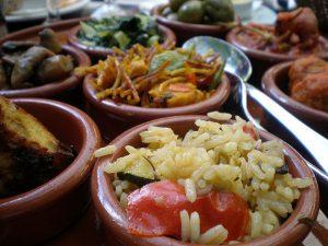 verschiedene Tapas in Tonschüsselchen wie Reis mit Gemüse, Tortilla, Paella, Fleisch in Tomatensauce