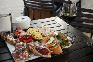 Terrassenholztisch auf dem ein weisser Aschenbecher, ein halb volles Weinglas und ein weisser viereckiger Teller mit verschiedenen Tapas auf Baguette steht