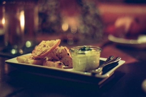 ein kleiner rechteckiger weisser Teller mit einem Gläschen das eine weiss-grünliche Sauce hat und getestete Brotscheiben daneben