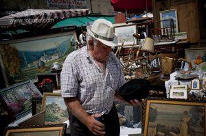 ein älterer Mann mit weißem Hut und kariertem kurzärmligen Hemd der gerade an einem Stand auf dem Enfants Wells einen schwarzen Hut in der Hand hält und begutachtet