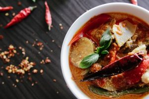 weisse Schüssel mit deftiger Suppe, schwarzer Tisch mit roten Chilischoten