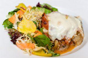 Mit Käse überbackene Pilze und gemischter Salat mit Sojasoßen darauf