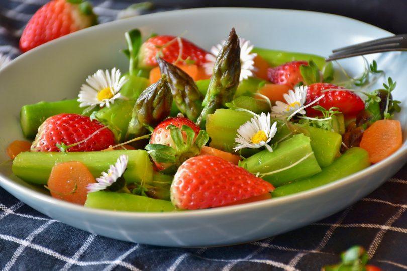 weisse Schüssel mit grünem Spargel, ganzen Erdbeeren und Gänseblümchen