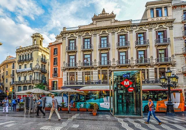 Aufzug einer Metrohaltestelle auf einem Platz in Barcelona, dahinter fährt ein torquier Bus vorbei und an der Seite ist eine Terrasse eines Cafés mit beigen Sonnenschirmen
