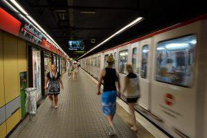 Foto einer Metrostation mit fahrendem Zug rechts und vereinzelten Fussgängern links