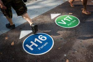Zwei farbige Kreise auf der Stasse gemalt, einer Blau der mit einem Pfeil zur Linie H16 Forum zeigt und einem grünen der mit einem Pfeil zur Linie V17 Port Vell zeigt