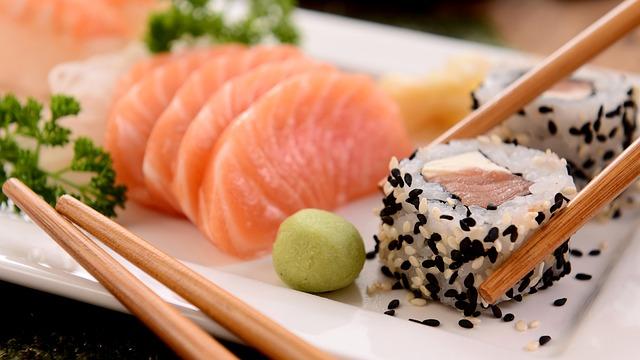 weisser Teller mit einer kleinen Wasabi Kugel, einem Maki mit weissem und schwarzem Sesamöl und Lach Sashimi