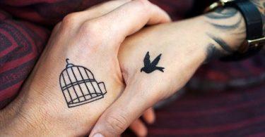 zwei Hände die sich die Hand geben eine hat einen offenen Vogelkäfig tätowiert und die andere eine fliegende Taube, und es schein als würde sie in den Käfig fliegen