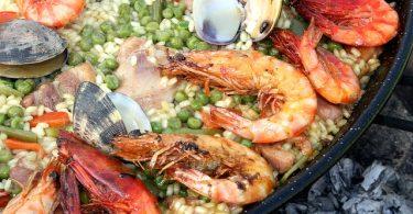 ein Ausschnitt einer großen Paellapfanne mit Reis und Meeresfrüchten wie Garnelen und Muscheln
