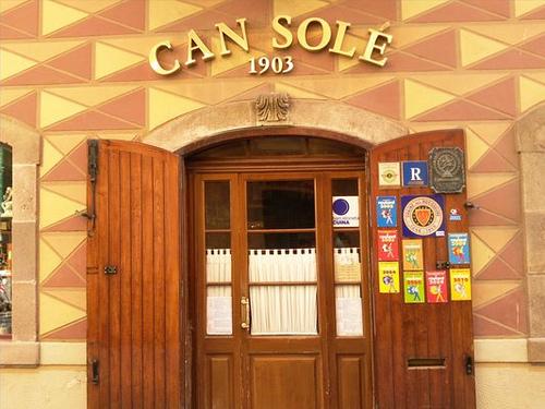 die Eingangstür des Restaurants Can Sole, Doppelte Holztüren, die äusseren sind geöffnet und die Inneren geschlossen, am rechte Türflügel kleben verschiedenen gastronomische Auszeichnungen