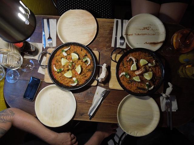 Tisch in einem Restaurant an dem vier Personen sitzen, auf dem Tisch ist Gedeckt mit runden Tellern, Besteck, weissen Servietten und in der Mitte stehen zwei Paellapfannen