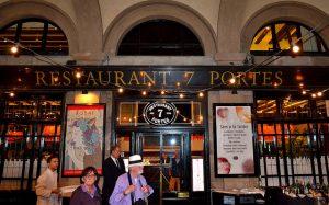 die Fasade des Restaurants 7 Portas mit schwarzen Fensterrahmen und goldener Schrift, einer Lichterkette davor und ein Kellner mit Krawatte an der Tür