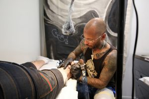 ein glatzköpfiger Tätowieren mit Brille der einer Person ein Tattoo auf die Wade sticht