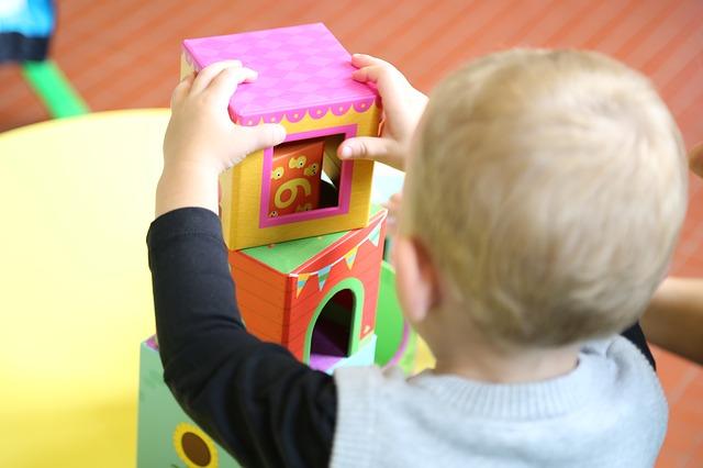 ein Kleinkind in Grau-Schwarz von hinten gesehen das gerade verschiedengrosse bunte Würfel aufeinander türmt