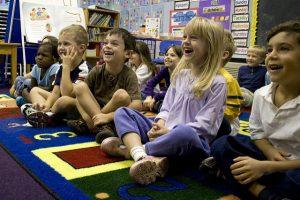12 Kinder von ungefähr fünf Jahren die auf einem bunten Teppich in einem Kindergarten sitzen und sich köstlich amüsieren