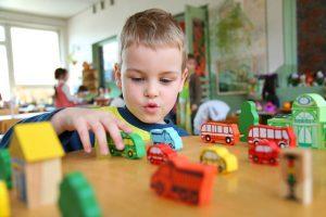 ein kleiner Junge der in einer Kita an einem Holztisch mit kleinen Autos spielt