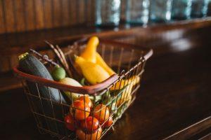 Kleines Einkaufskörbchen auf einem Tressen gefüllt mit Zucchini, Kirschtomaten und kleinen Kürbissen