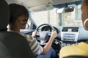 eine junge Frau mit grau-weiss gestreiften T-Shirt die beide Hände am Lenkrad eines Autos hat und daneben sitzt eine Frau im gelben Pullover die beobachtet wie sie fährt