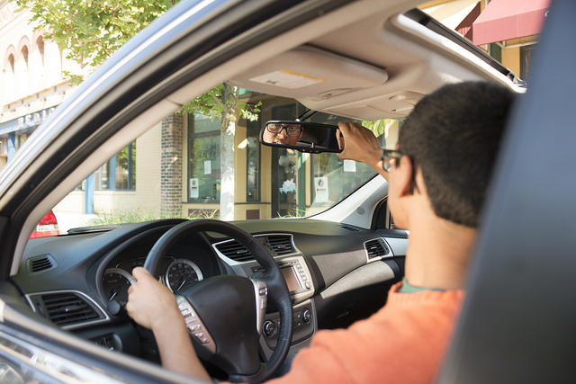 ein junger Mann mit Brille und orangenem T-Shirt der in einem Auto sitzt und die linke Hand am Lenkrad hat und sich mit der rechten den oberen Spiegel zurecht rückt
