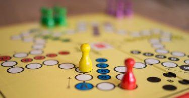 ein Mensch ärgere dich nicht Brettspiel mit verschiedenfarbigen Spielfiguren - gelb, rot, grün, lila- die auf dem dem Brett verteilt sind