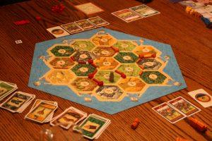 das sechseckiges Strategiespiel Catan auf einem Holztisch mit Spielkarten drum herum