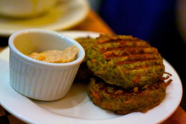 drei Hamburger, der dritte liegt auf den anderen zweien und daneben ein kleines weisses Schüsselchen mit einer orangenen Sauce