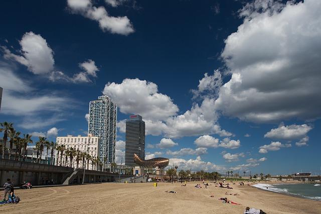 der Strand der Barceloneta mit Mensche die genüsslich in der Sonne liegen
