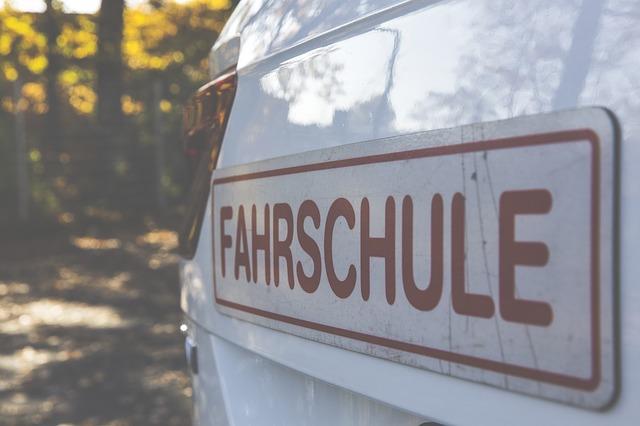 Nahaufnahme der hinteren Teils eines weissen Fahrschulautos auf dem ein großer Aufkleber mit roter Schrift klebt auf dem Fahrschule in Großbuchstaben steht