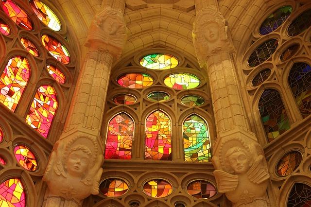 in der Mitte farbige Mosaikfenster und an den weißen Säulen Statuen von Engeln